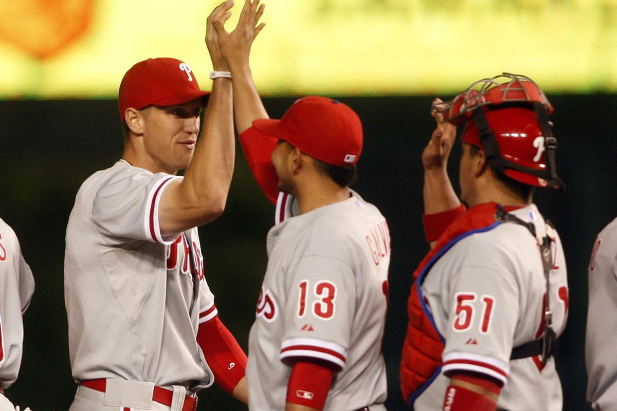 May 17, 2012; Chicago, IL, USA; Philadelphia Phillies players Hunter Pence (left) celebrates with teammates Freddy Galvis (13) and Carlos Ruiz (51) after defeating the Chicago Cubs 8-7 at Wrigley Field. Mandatory Credit: Jerry Lai-US PRESSWIRE