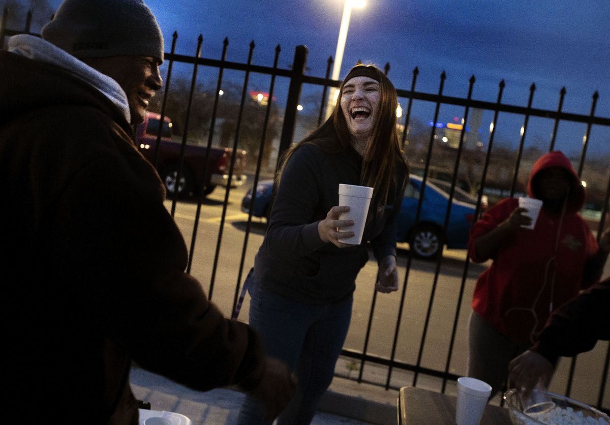 Natalie Clark laughs while passing out hot chocolate and sandwiches to people on the street near the Road Home shelter in Salt Lake City on Tuesday, Nov. 12, 2019. Clark and a group of foster children from the DCFS Transition to Adult Living Program were feeding the homeless that night. Transition to Adult Living provides youths assistance in transitioning from foster care to adult living.