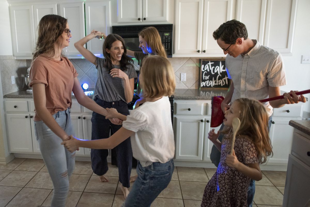 Under the glow of a strobe light, the Jacobs family participates in a dance party in their kitchen inside their home near Austin, Texas, Tuesday, Nov 24, 2020. The family dances together everyday to help boost energy and morale.
