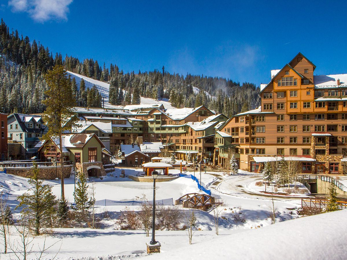 A stairstepping condo complex sits at the base of a ski resort with snow covering everything.
