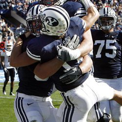 Brigham Young Cougars quarterback Riley Nelson, with back to camera, is congratulated by teammates after he runs in for a touchdown as Brigham Young University faces Idaho State in NCAA football in Provo, Saturday, Oct. 22, 2011.