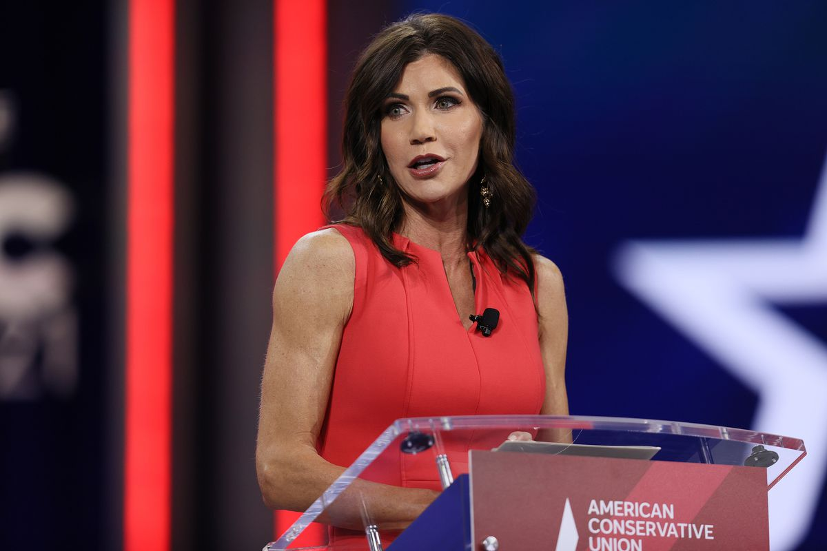 Noem speaks at a clear acrylic platform with a red-white-and-blue backdrop, wearing a sleeveless red dress and a lapel mic.