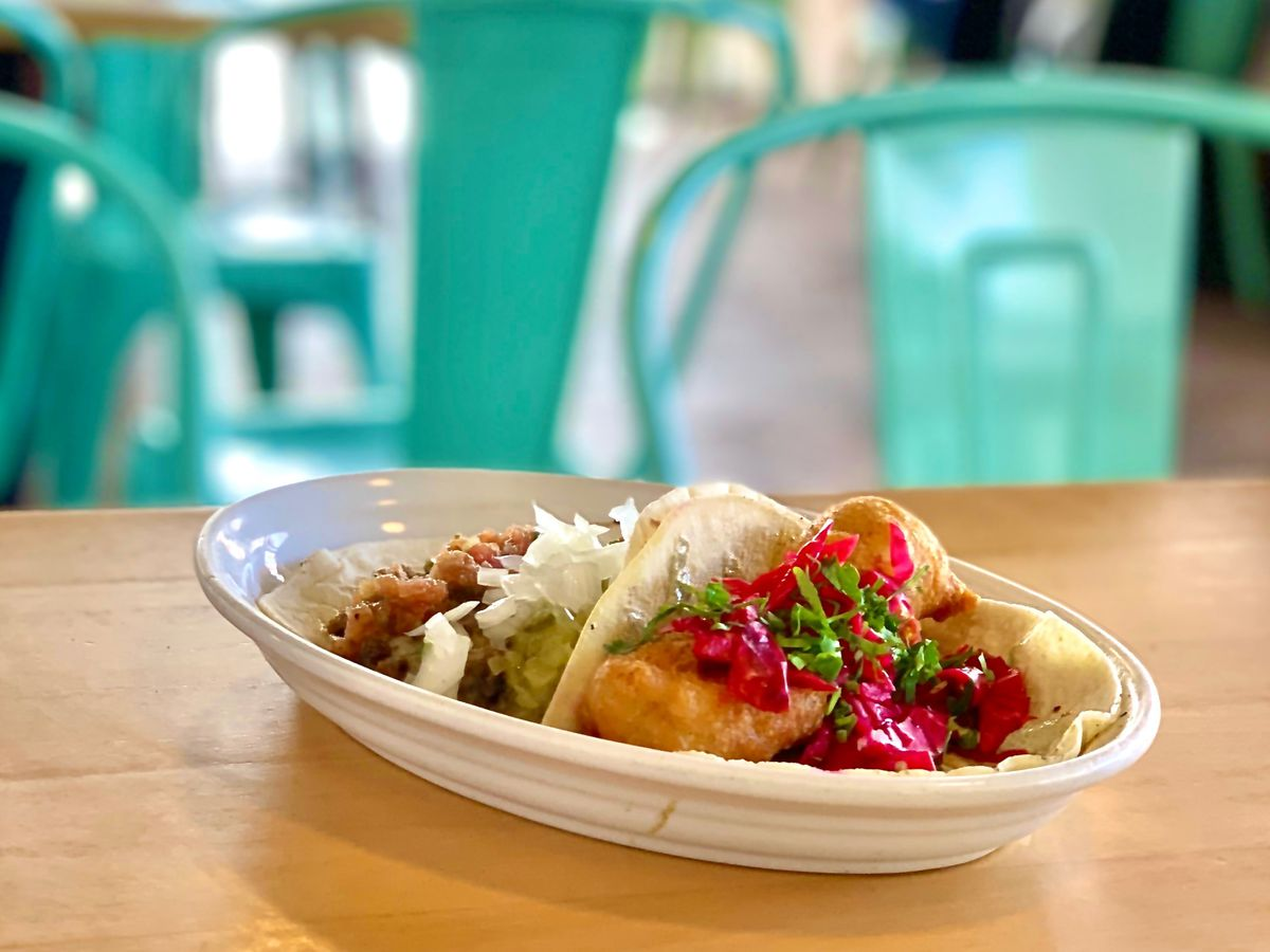 A plate of tacos on a table beside brightly colored metal seats