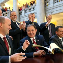 Gov. Gary Herbert passes a copy of SB296 to Lt. Gov. Spencer Cox after signing it at the Capitol in Salt Lake City on Thursday, March 12, 2015.