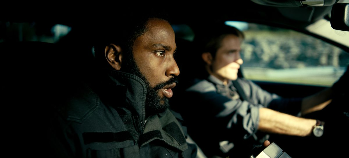 John David Washington and Robert Pattison sit in a car in Tenet
