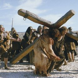"""This promotional photo provided by Marquis Films shows actor Jarreth Merz, who plays Simon of Cyrene, right, help actor Jim Caviezel, portraying Jesus Christ, carry a cross during a scene from Mel Gibson's """"The Passion of the Christ,"""" in this Jan. 24, 2003, file photo."""