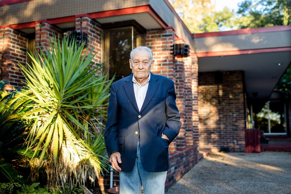 Albert Ledner stands in front of the Leonard House, a brick home with red accent.