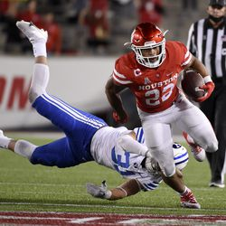 Houston running back Kyle Porter (22) escapes a tackle by Houston defensive lineman Derek Parish during the first half of an NCAA college football game, Friday, Oct. 16, 2020, in Houston.