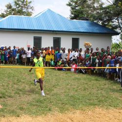 A young girl runs to jump over the bar in a donated Jr. Jazz jersey at the Sports Festival in Abomosu, Ghana.