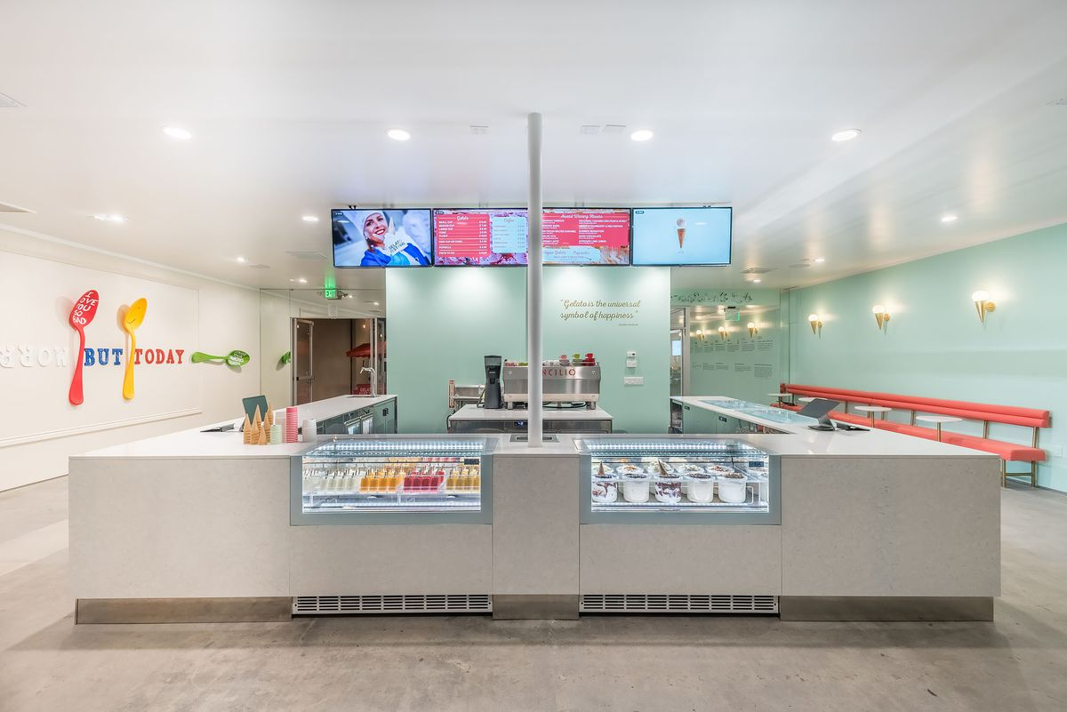 An open ordering counter filled with gelato trays.