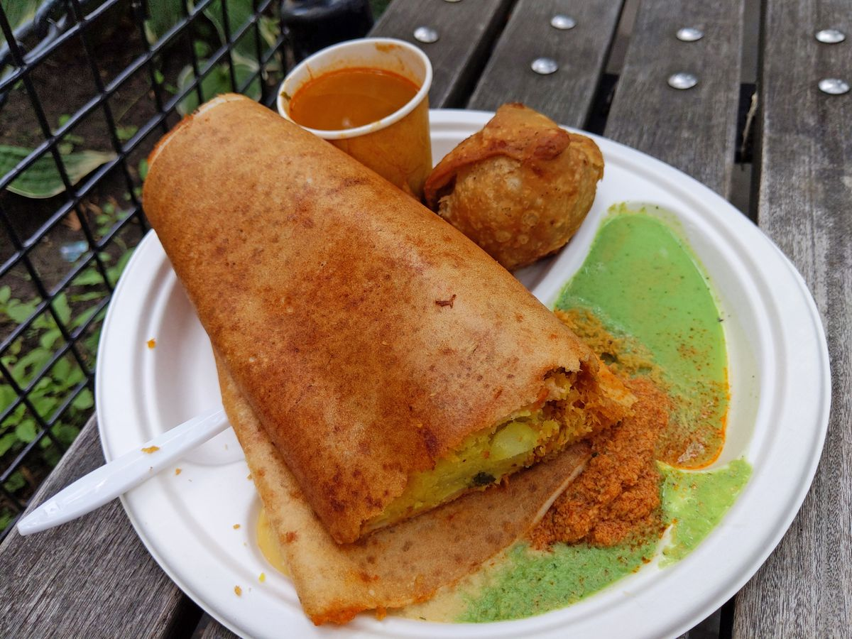 A white paper plate placed on a wooden bench with a dosa on it, a green cilantro sauce, a samosa, and a red sauce in a plastic cup