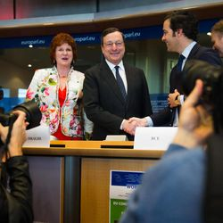European Central Bank President Mario Draghi, center, smiles as he arrives to address the committee on economic and monetary affairs at the European parliament in Brussels, Wednesday April 25, 2012.