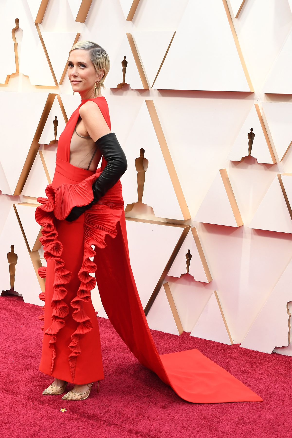 Kristen Wiig poses on the Oscars red carpet.