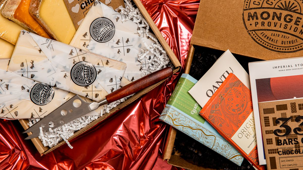 Cheese wrapped in Mongers' Provisions paper with a cheese knife and a separate box filled with assorted chocolate bars.