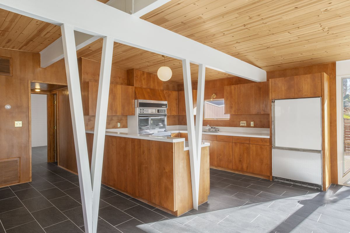 A kitchen has white, V-shaped beams, wood cabinets, white countertops, and white vintage appliances.