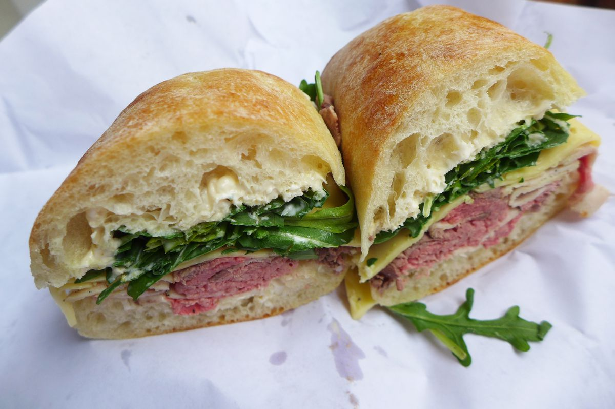 A sandwich on a demi baguette cut to show pink meat in the center.