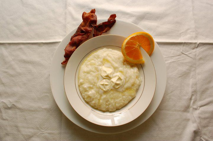 A bowl of grits with a side of bacon and an orange slice