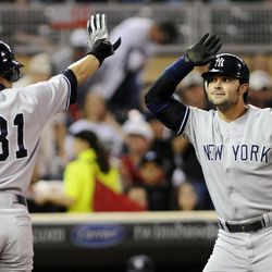 New York Yankees' Ichiro Suzuki, left, of Japan, congratulates Nick Swisher after Swisher's two-run home run off Minnesota Twins pitcher Liam Hendriks in the first inning of a baseball game, Monday, Sept. 24, 2012, in Minneapolis.