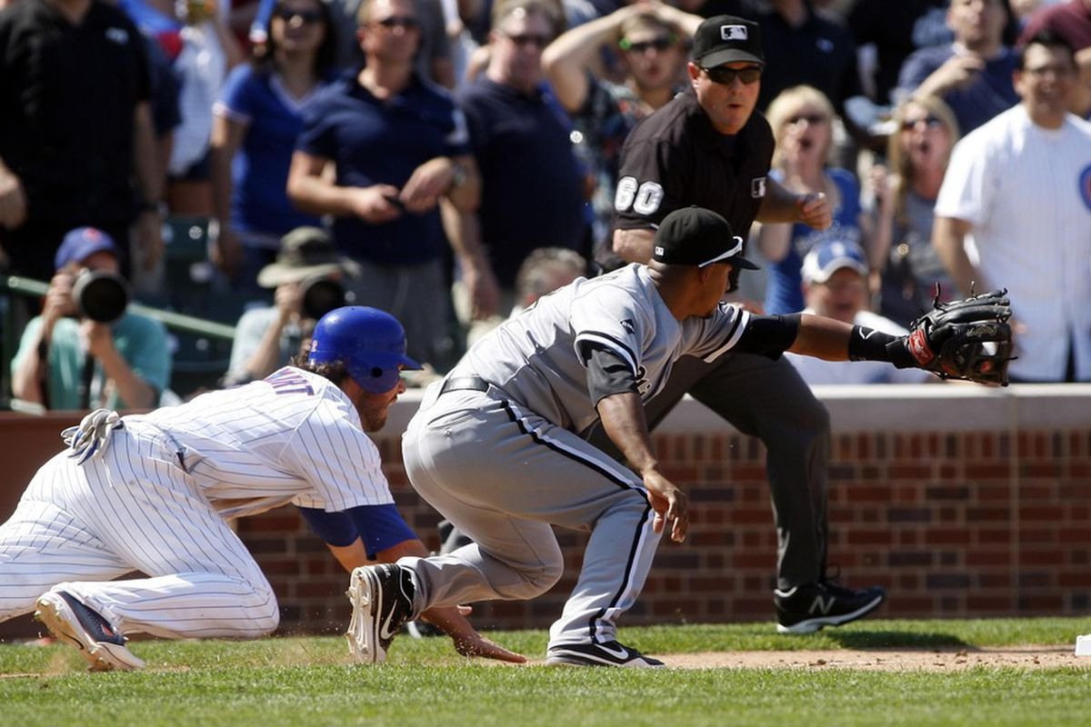 Chicago, IL, USA; Chicago Cubs third baseman Ian Stewart dives back into third base ahead of the tag by Chicago White Sox infielder Eduardo Escobar at Wrigley Field. Credit: Jerry Lai-US PRESSWIRE