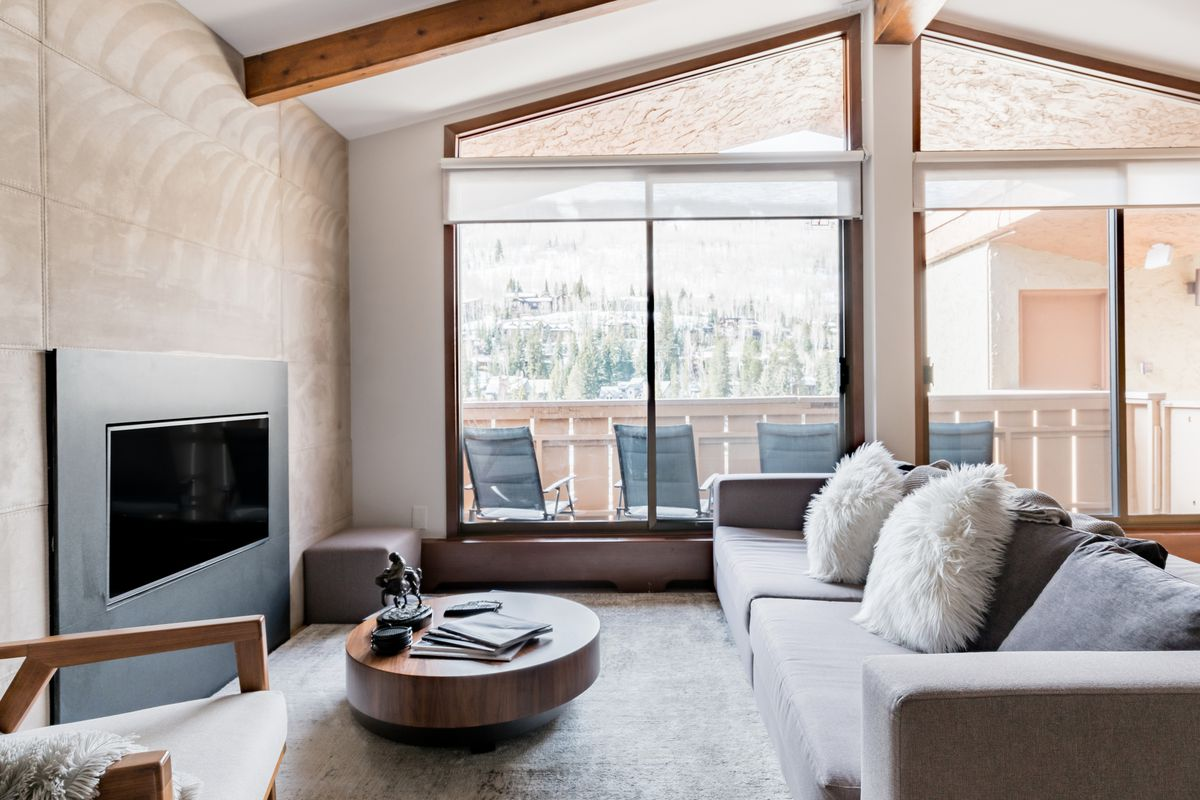 An interior photo of a condo living room. There is a gray couch with fluffy white pillows, a round coffee table, and a modern black fireplace. A balcony is in the background.