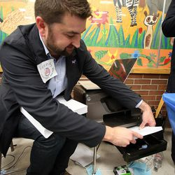 Kenny Wilks places more paper in a printer at a Democratic caucus at Emerson Elementary School in Salt Lake City on Tuesday, March 22, 2016. The location ran out of ballots and had to print more on site.
