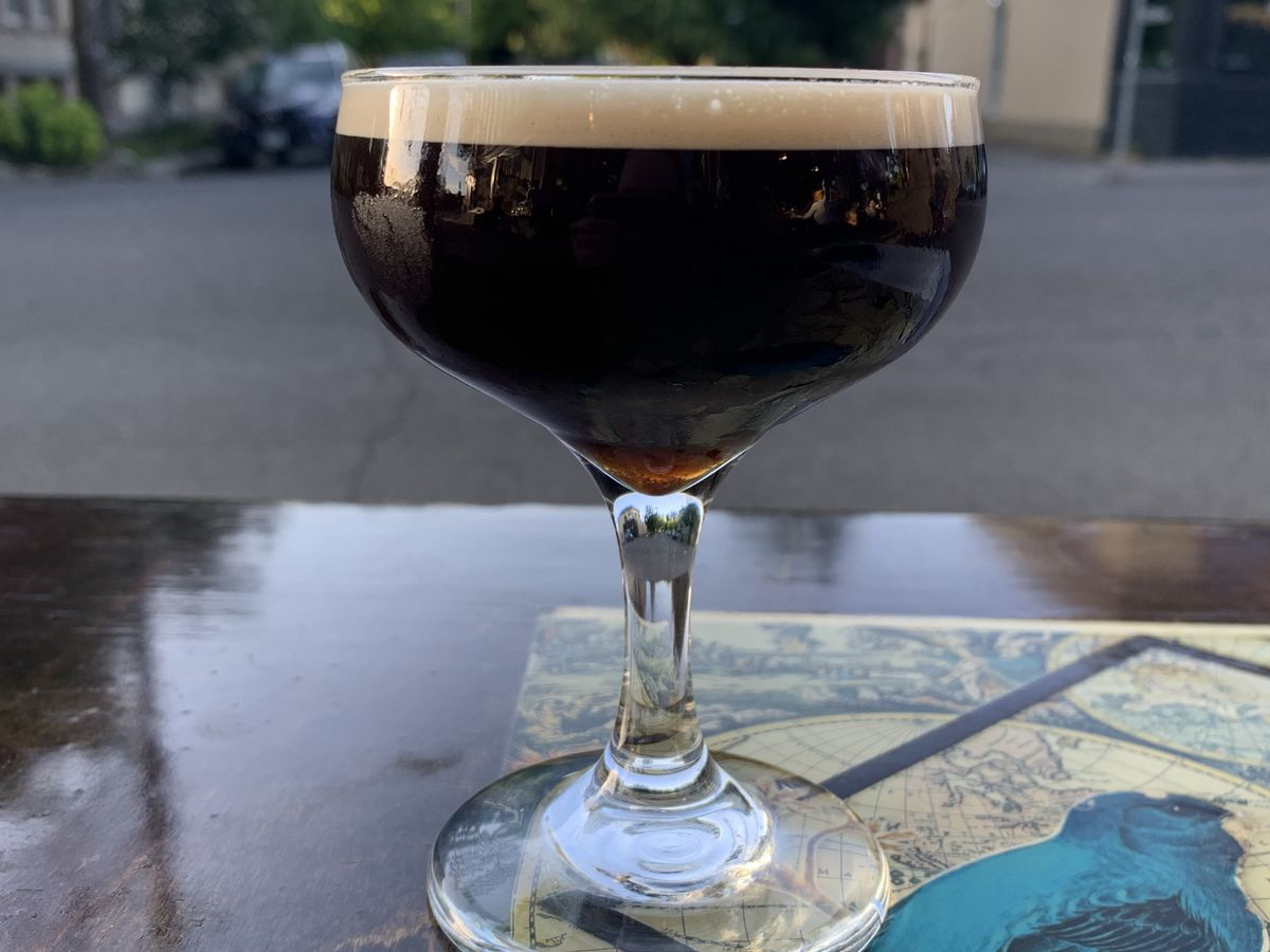 A coupe glass holds a dark, nearly black, cocktail with a head of pale foam. The glass sits on a shiny wooden table, with a street in the background.
