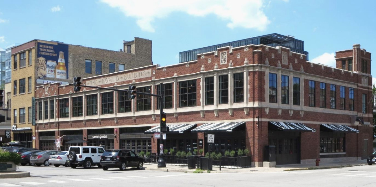 """A two-story commercial building with a brick facade and stone details. It has ground-floor retail space and a stone sign reading """"The Howard Building."""""""