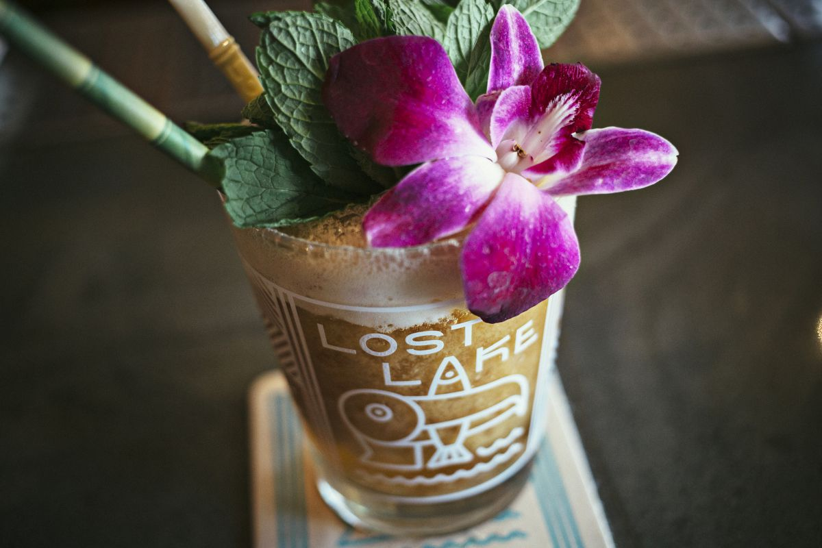 A brown tiki cocktail inside a clear glass with the Lost Lake logo, colorful straws, and flower and herb garnishes.