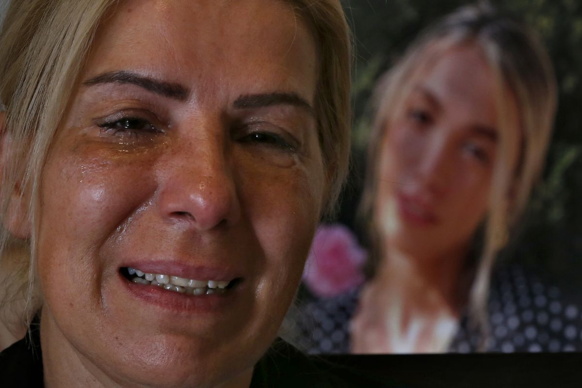 Chouchan Yeghiyan weeps in front of a picture of her daughter Jessica Bezdjian, who was killed in last year's massive blast at Beirut's seaport. Bezidjian was one of four female nurses whose lost their lives at the Saint George Hospital University Medical Center that day, including her close friend Jessica Kahwaji.