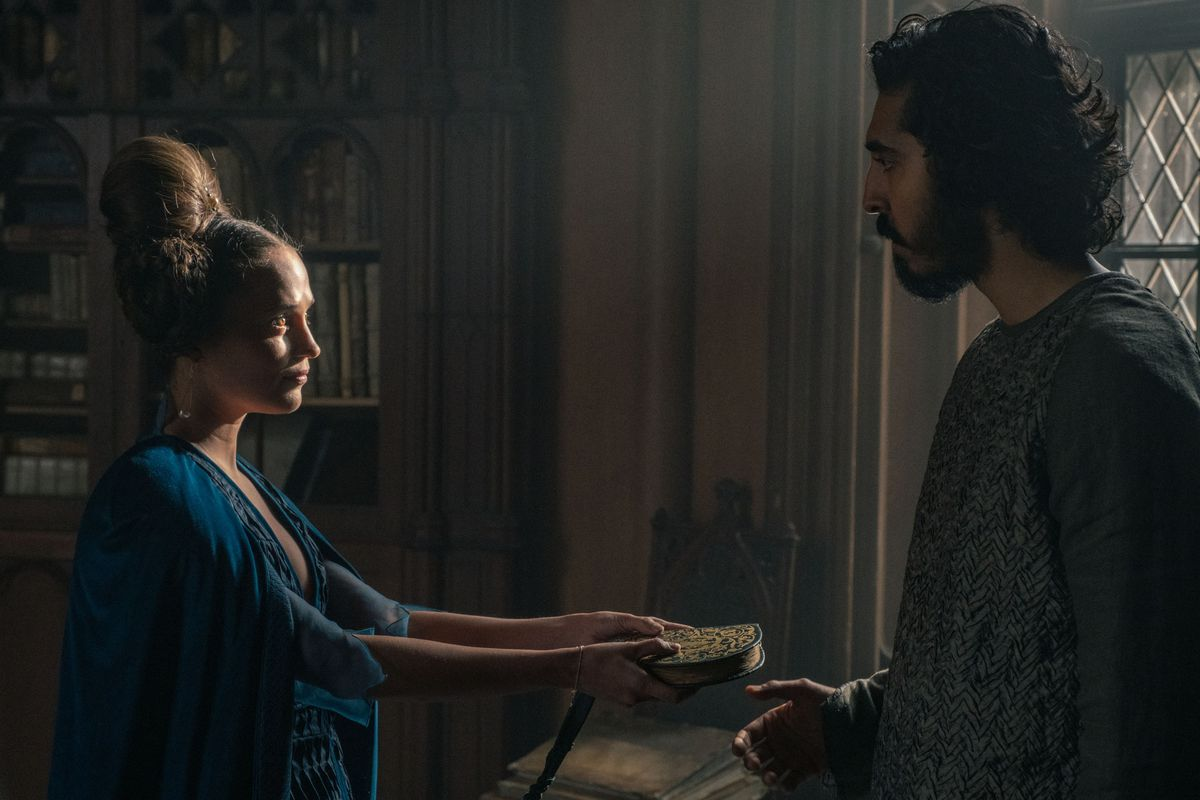 Alicia Vikander hands Dev Patel a book of love poems in The Green Knight