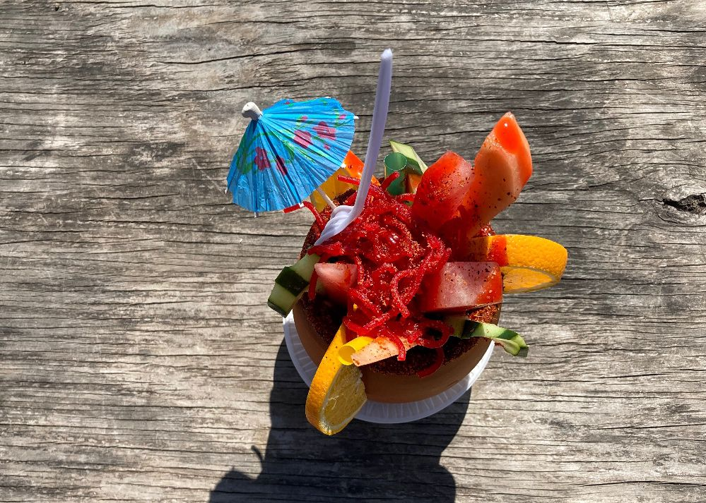 an umbrella, fruit, and various vegetables hang out of a terra cotta cup.