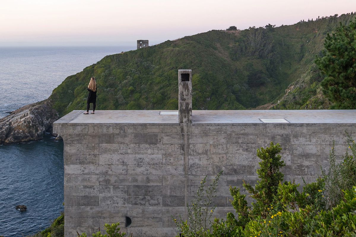 Simple rectangular volume made of raw concrete juts out of mountainside on cliff overlooking the beach.