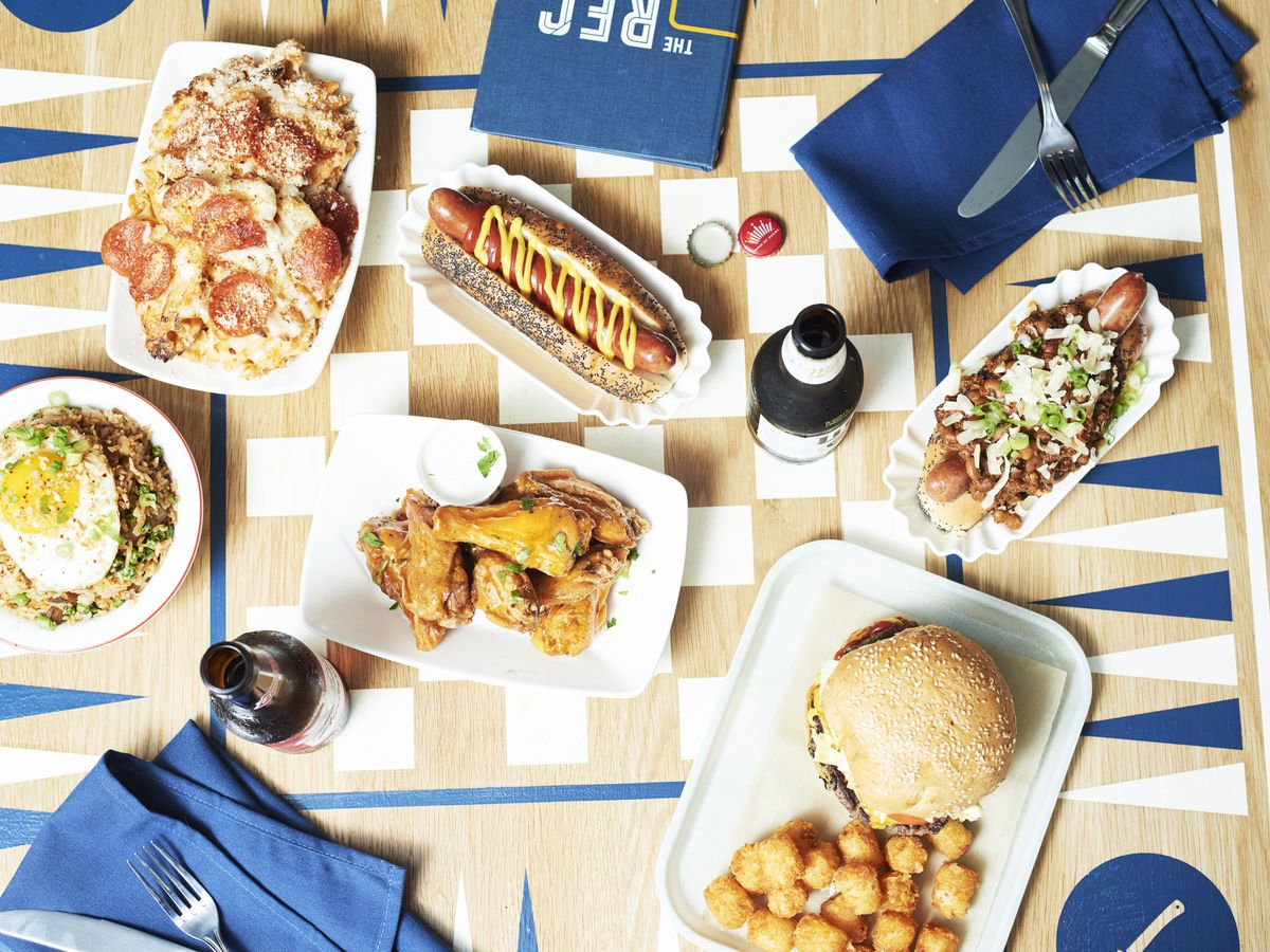 a wood, blue, and white game table covered with plates of hot dogs, pizza fries, burgers, wings, and bottles of beer