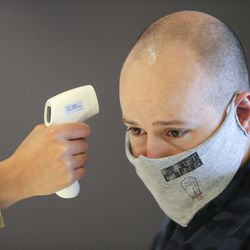 Salt Mine Productive Workspace Vice President Jacob Bonesteel has his temperature checked at the business in Sandy on Wednesday, May 13, 2020.
