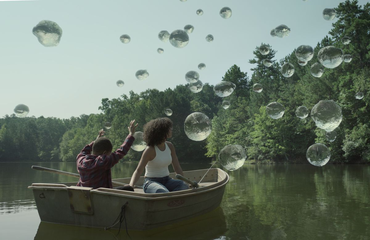 a mother and son sit in a rowboat on a lake, surrounding them are large bubbles. the son lifts his hands, as if he is controlling them