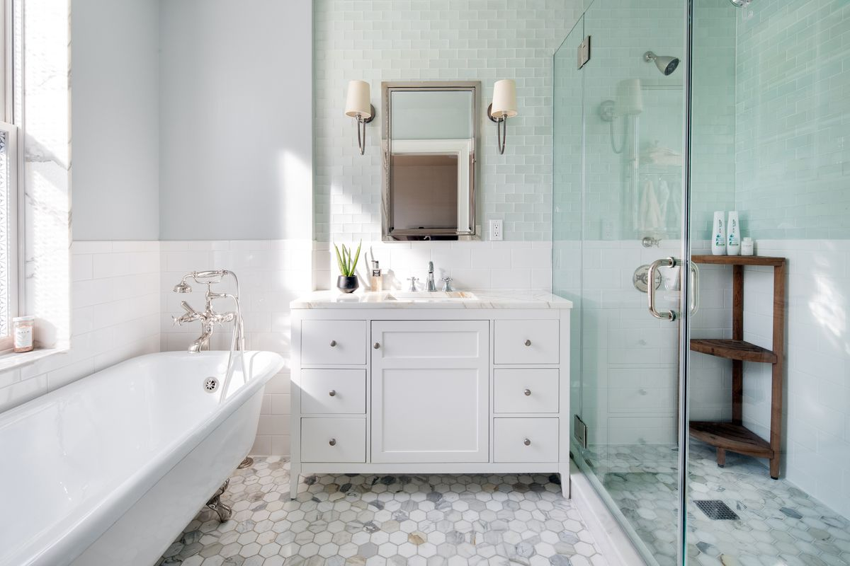 A bright bathroom attached to the master bedroom features a white clawfoot tub, single vanity, and glass enclosed shower.