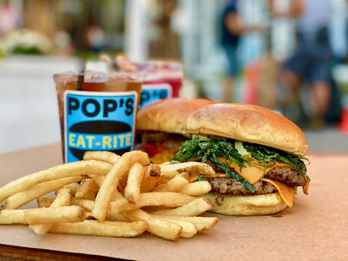 Two burgers, a side of fries, and two soft drinks sit on brown parchment paper outdoors, while a city street is blurred in the background
