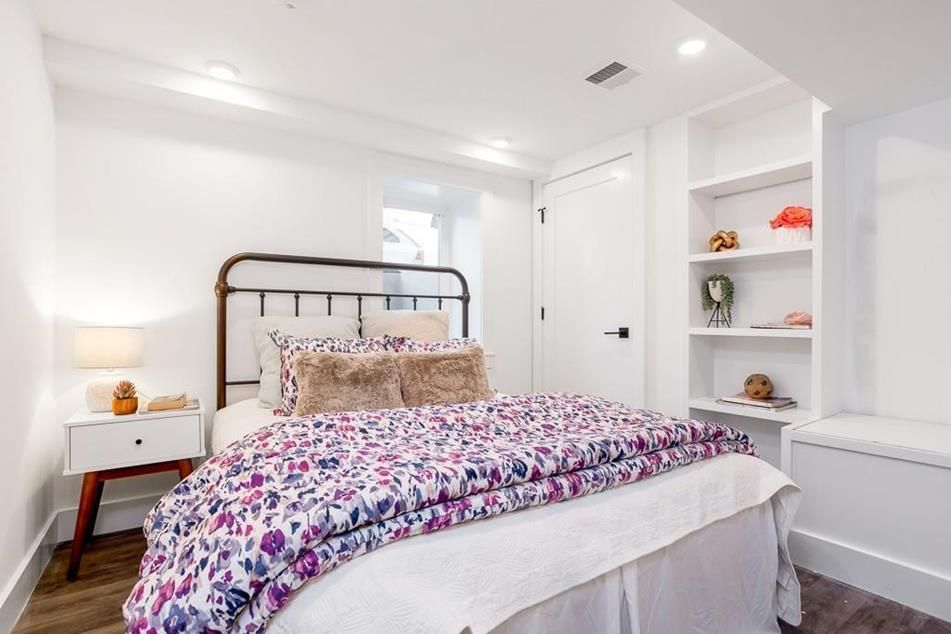 A bedroom with a bed and shelving.