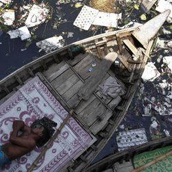 A boatman sleeps in his boat anchored in the polluted waters of the River Buriganga in Dhaka, Bangladesh, Sunday, April 22, 2012. April 22 is observed as Earth Day every year as a tool to raise ecological awareness.