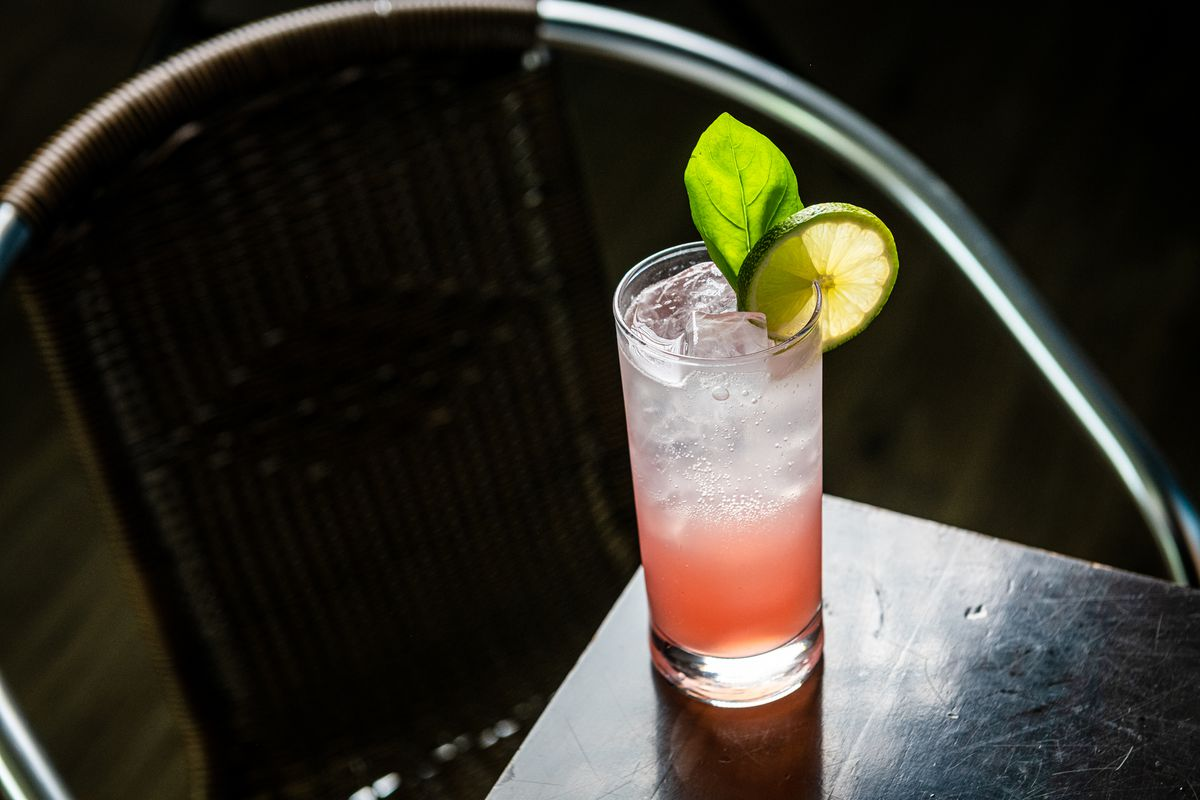 A highball glass full of clear soda and a hibiscus and black cardamom syrup at Daru