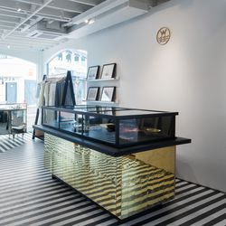 Local painter Christopher Lord hand-painted the shoefie-friendly striping on store's concrete floors, while Venice creative studio Dust to Dust crafted this custom brass tiled cash wrap.