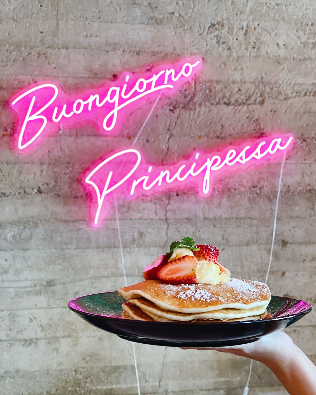 """Person holding a plate of pancakes in front of a neon sigh that says """"Bonjour Principessa"""""""