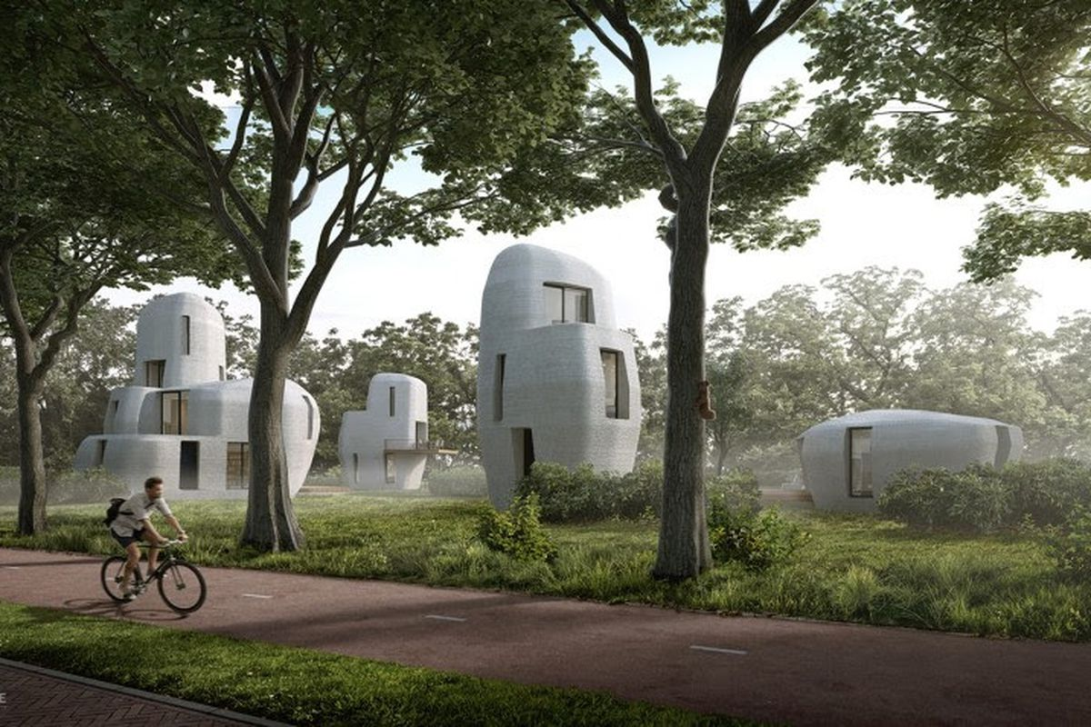 3D printed stone homes with biker in front of them