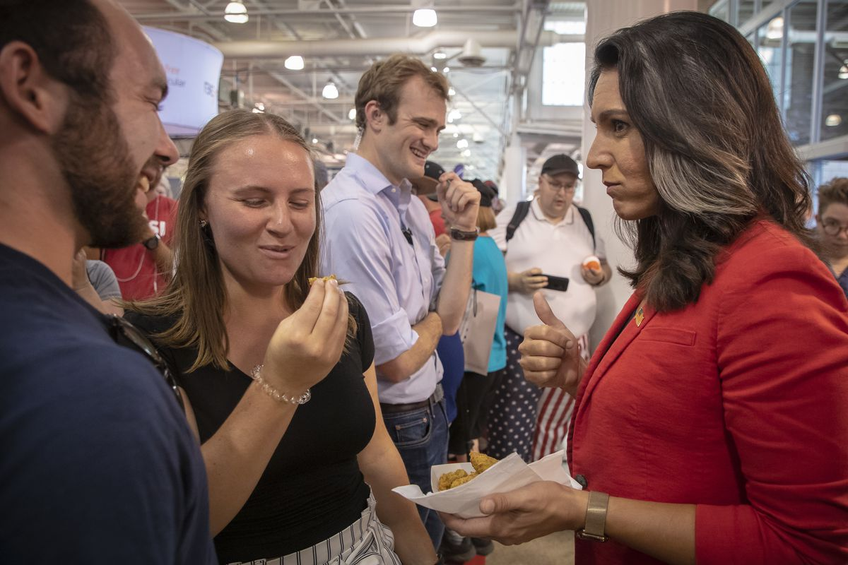 Tulsi Gabbard shares her avocado slices with a man and a woman, and gives a thumb's up sign.