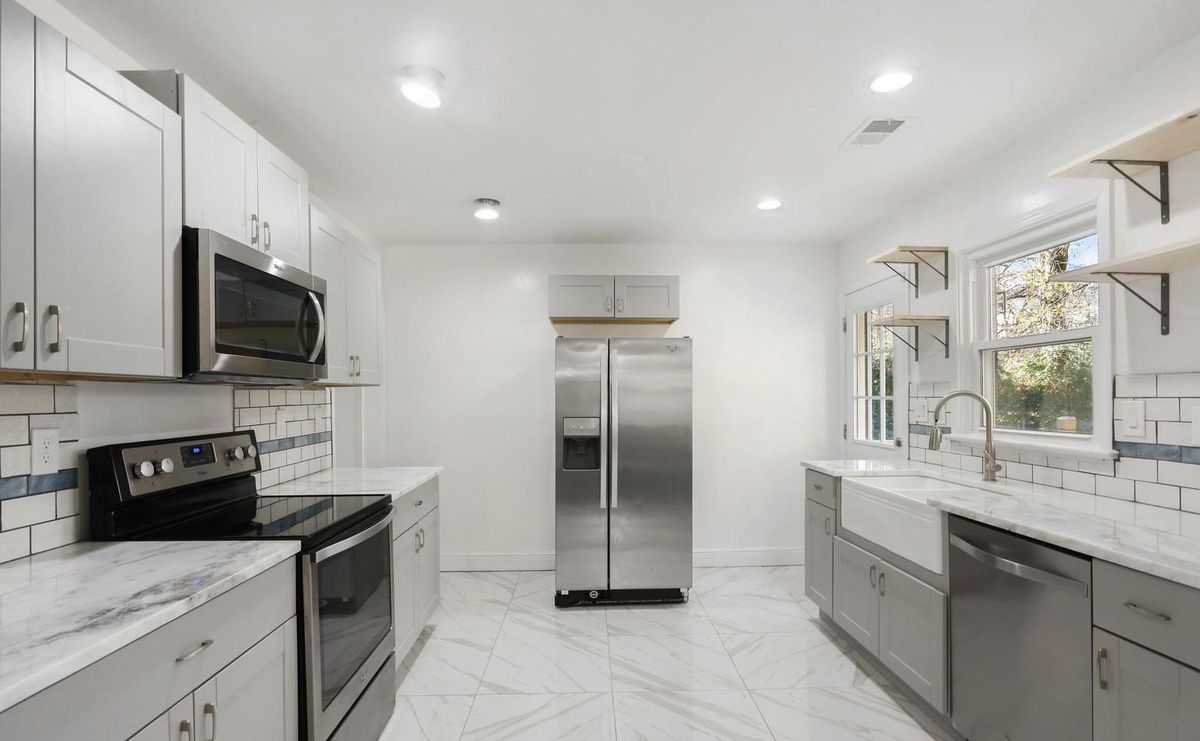 White kitchen with marbled countertops, white farmhouse sink, black and stainless appliances, and tiled floor.