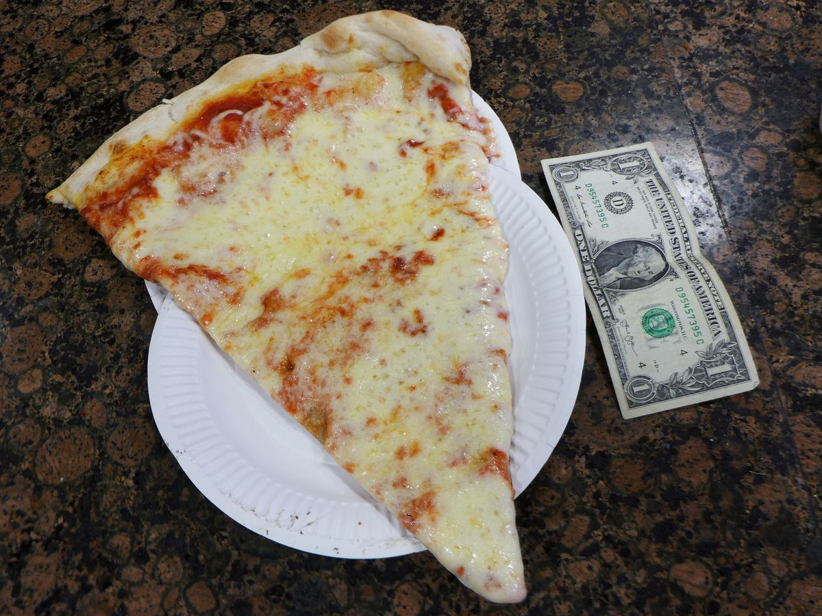A slice of pizza next to a dollar bill to show size.
