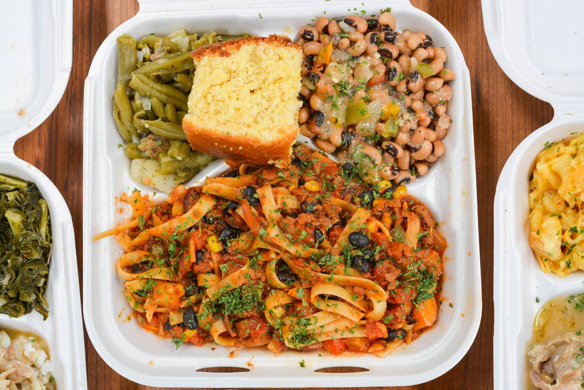 A styrofoam platter loaded with rich pasta, green beans, and other comfort foods.