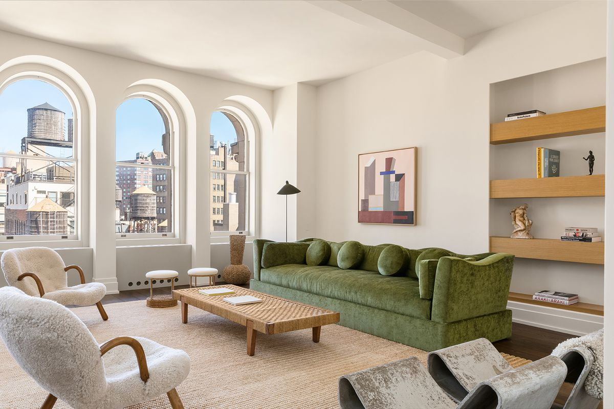 A living area with arched windows, high ceilings, a light brown rug, and a green couch.