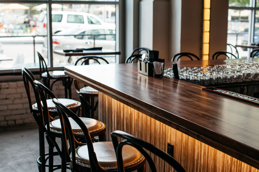 A wooden bar surrounded by wicker-style bar stools in dark wood tones.