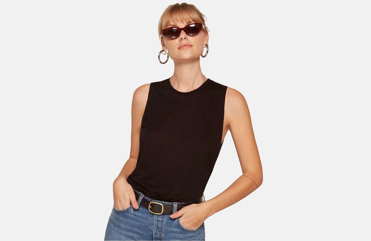 A model in a black tank top, sunglasses, and jeans